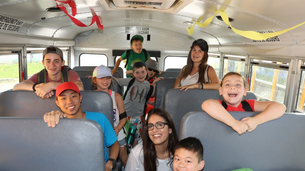 Campers arrive at Camp Robin Hood by bus.