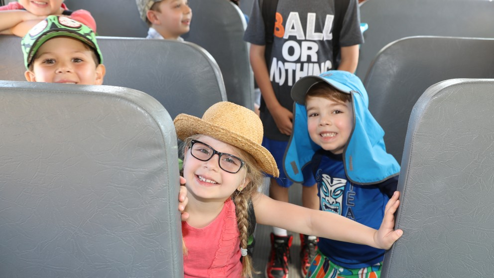 Campers smile on the camp bus