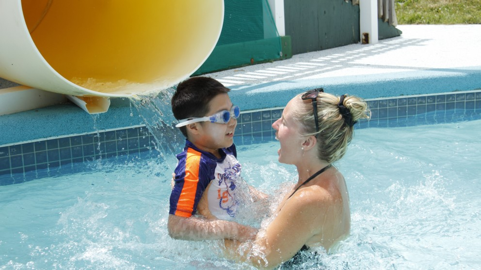 A Swimming Instructor helps a camper overcome his fear of the waterslide.
