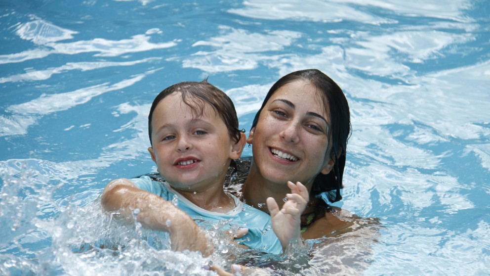 One of our highly trained swimming instructors helps a young camper learn how to swim.