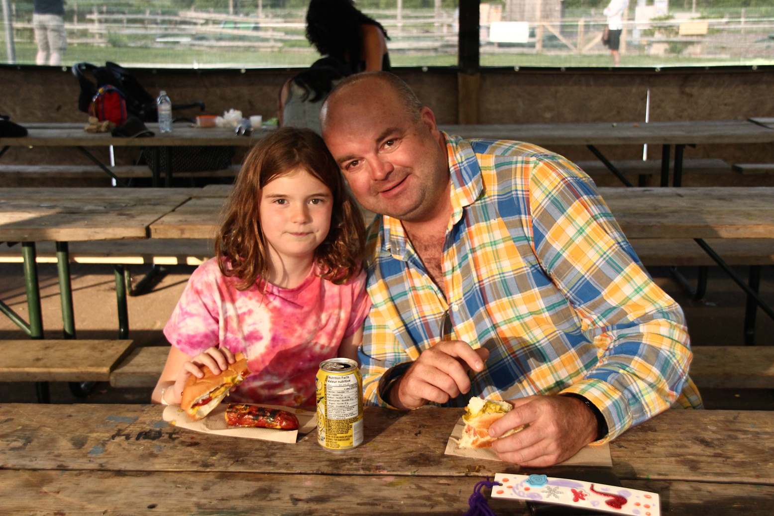 A father and daughter enjoy a hot dog together at Camp Robin Hood during one of our open house events where parents can see why kids think this is the best camp in the world!
