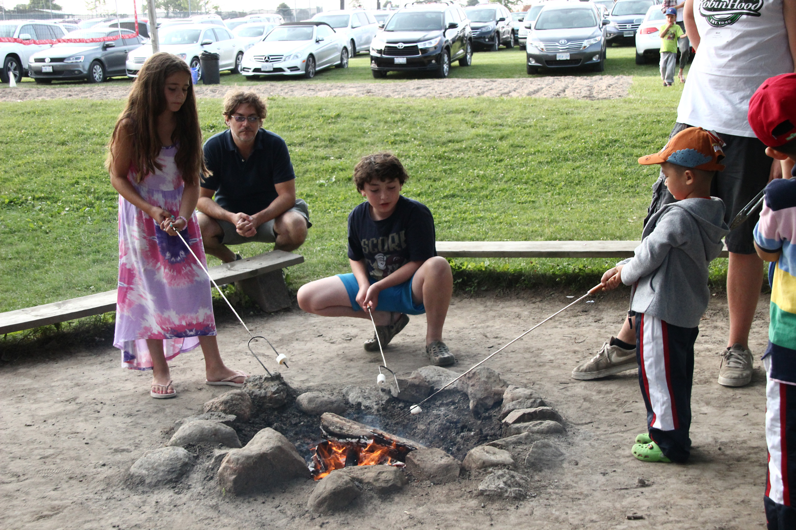 A girl and boy roast marshmallows on a long stick over a campfire at Camp Robin Hood. This camp provides traditional outdoor camp-style activities but is a day camp where children go home each night on free door-to-door bus service.
