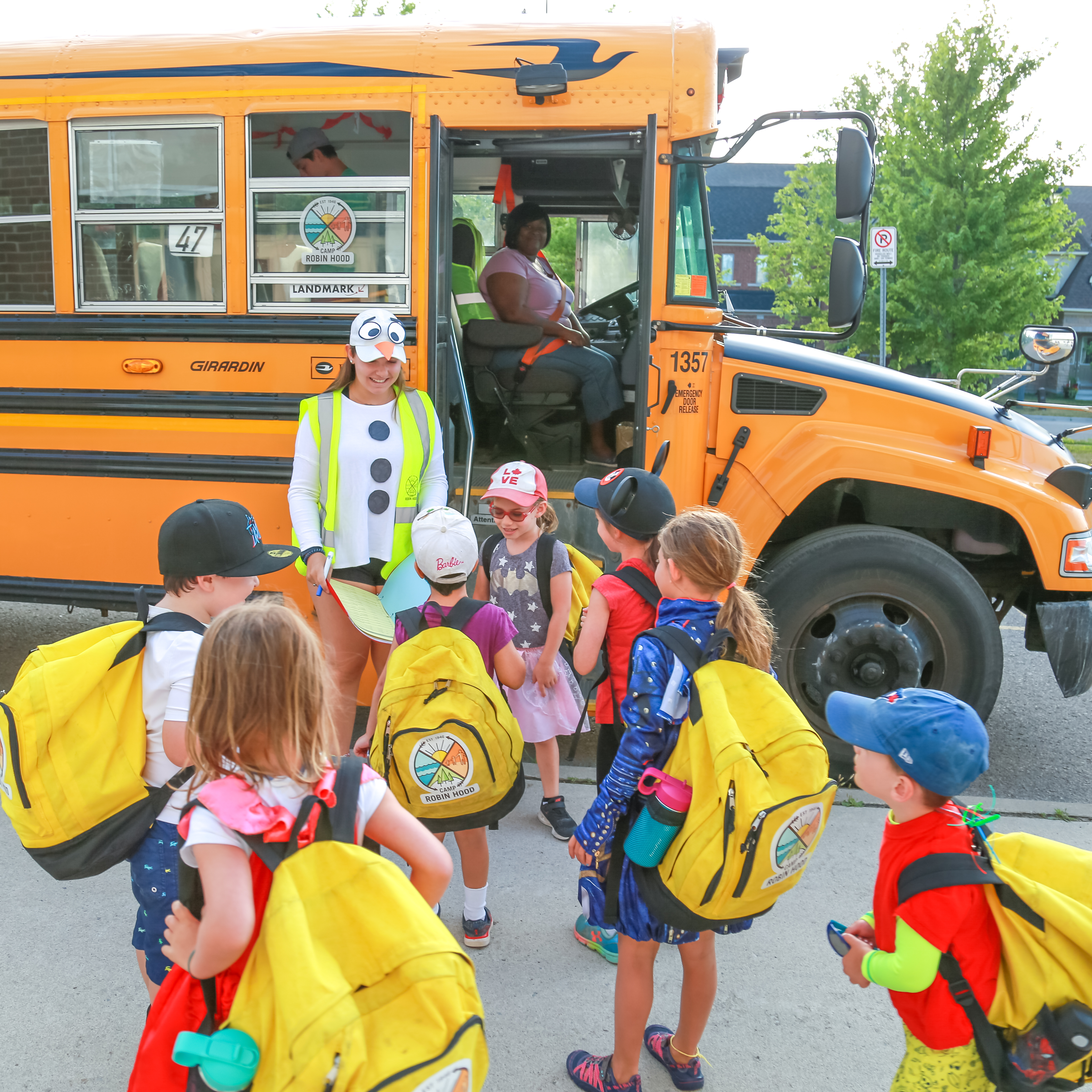 A group of campers wait with a staff member to board their bus to camp